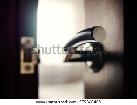 A close-up of the doorway and the door handle, shallow depth of field. - stock photo