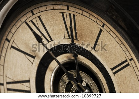 A Close-up of the face of an antique grandfather clock that is going to strike midnight shortly - stock photo