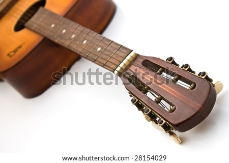 A close up of the headstock and fretboard of a wooden acoustic guitar. - stock photo
