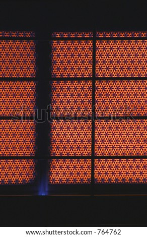 A close up of the heating ceramic of a switched on gas heate in portrait moder, with silhouette of grille.