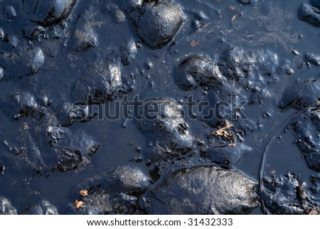 A close up of the surface of black oil pollution. - stock photo