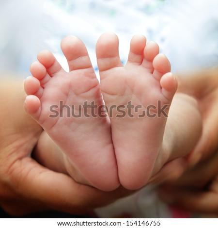 A close-up of tiny baby feet  - stock photo