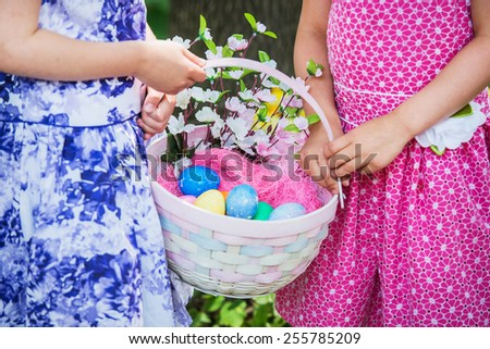 A close up of two little girls hands holding a basket with Easter eggs and flowers in the spring season outside in a beautiful garden setting.    Part of a series.  - stock photo
