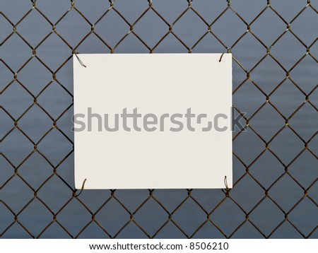 A close up on a blank sign attached to a chain link fence. - stock photo