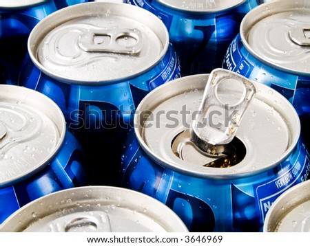 A close up on a bunch of soda cans. One of the cans is open. - stock photo