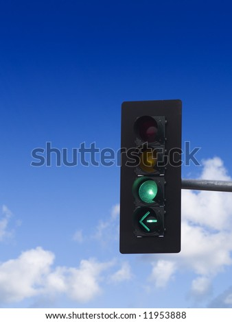 A close up on a green traffic light with blue sky and clouds in the background. - stock photo