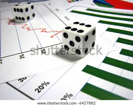 a close up on a pair of white dice that are on top of different types of graphs. The main light is in the front die. - stock photo