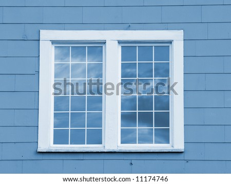A close up on a single window with clouds reflected in the glass. - stock photo