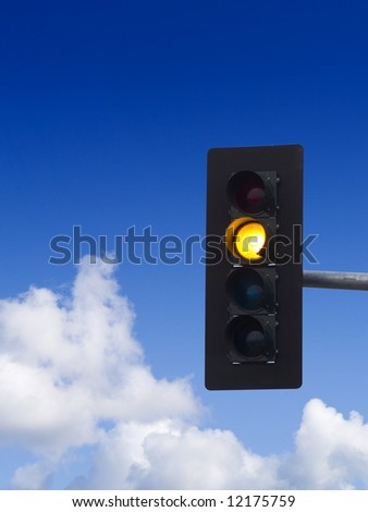 A close up on a yellow traffic light with blue sky and clouds in the background. - stock photo
