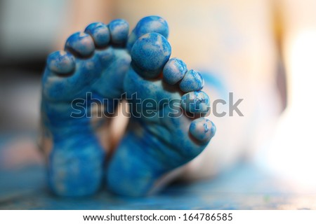 a close up on the bottom of the feet of a small child, that have been painted blue.  Very shallow depth of field with focus on toes of front foot. - stock photo