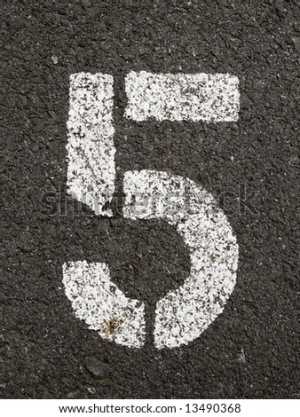 A close up on white stenciled number five on black pavement. - stock photo