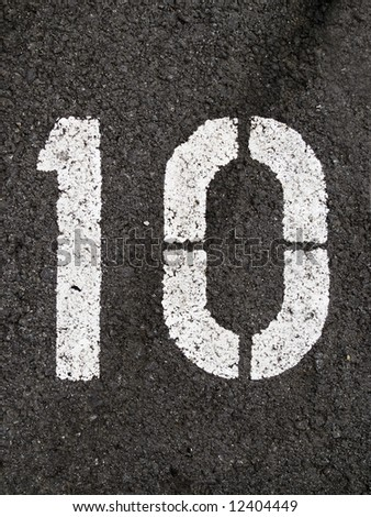 A close up on white stenciled number ten on black pavement. - stock photo
