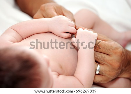 A close up photo of a fair skinned new baby holding his dark skinned father's fingers.