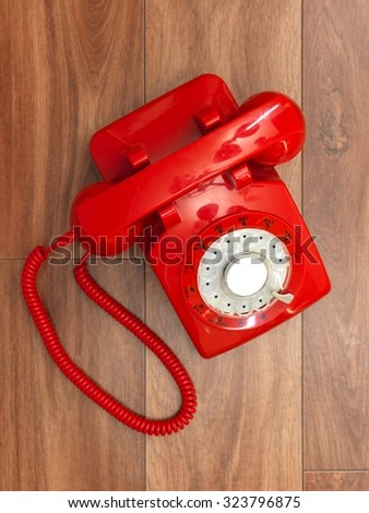 A close up photo of a red rotary phone - stock photo