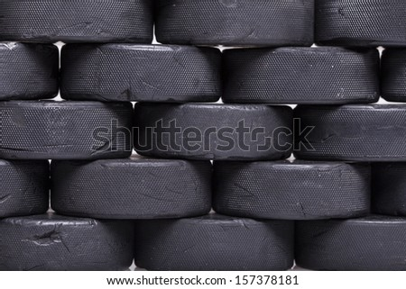 A close up photo of a wall of well used hockey pucks.