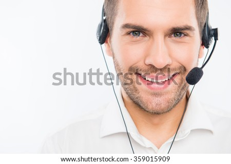 A close-up photo of smiling young agent of call centre - stock photo