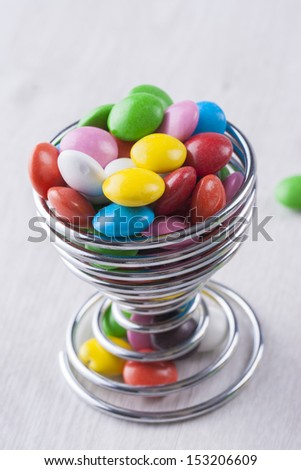 A close up photo of the junk food - a multicolor chocolate on a bright wooden background.