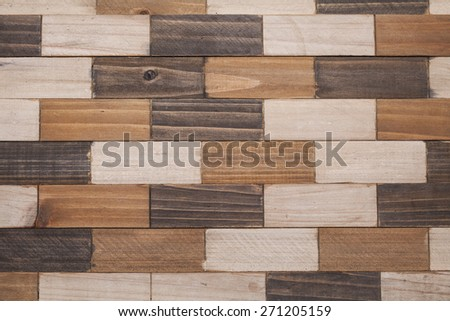 A close up photograph of a checkered wood pattern. Different shades of brown stain were used on this rustic pattern. - stock photo