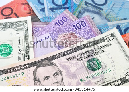 A close-up photograph of Australian dollars, US dollars and Malaysia's ringgit Malaysia currency.