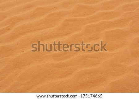 A close-up photograph of corrugated drawing on the sand of the desert. - stock photo