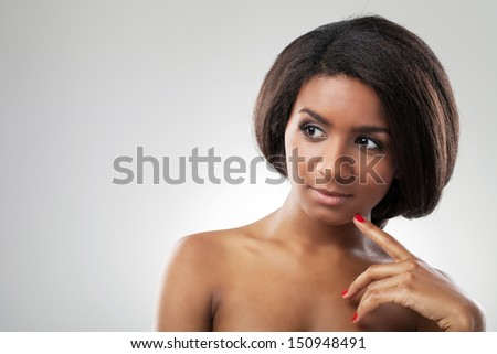 A close up portrait of a beautiful dark-skinned woman is touching her naked shoulder - stock photo
