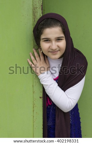 A Close up Portrait of a Beautiful Muslim Girl In Front of a Green Doorway - stock photo