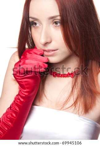 A close-up portrait of a beautiful redhead woman in red gloves - stock photo