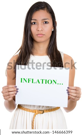 A close-up portrait of a beautiful serious woman holding a sign which says inflation, isolated on a white background  - stock photo