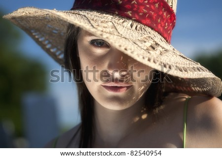 A close up portrait of a beautiful twenty something young woman in a sun hat with one eye showing. - stock photo