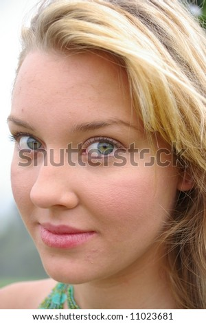 a close-up portrait of a beautiful young fashionable blond girl