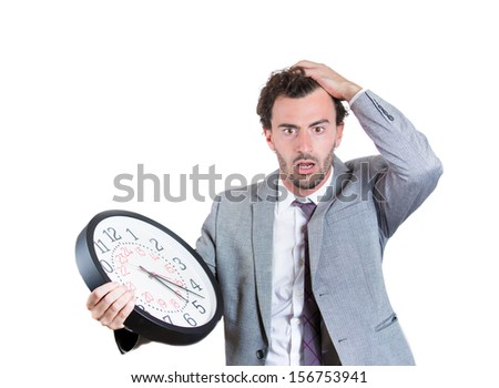 A close-up portrait of a businessman, executive, leader holding and looking anxiously at a clock, stressed and worried, pressured by lack of time, running out of time, isolated on white background - stock photo
