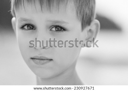 A close up portrait of a handsome thoughtful little boy, black-and-white photo  - stock photo