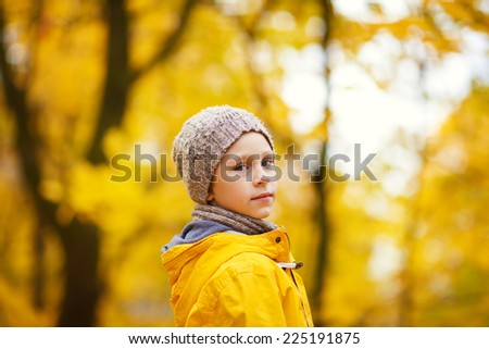 A close up portrait of a little cute boy in a bright yellow jacket and grey knitted hat in a park on a sunny autumn day - stock photo