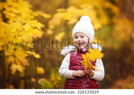 A close up portrait of a little cute girl in a bright red jacket and a knitted white hat walking in a park on a sunny autumn day