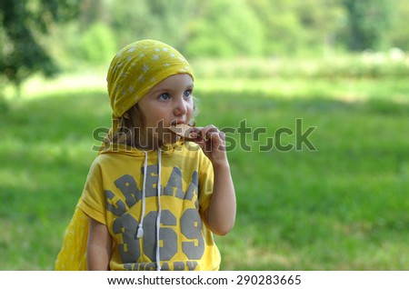A close up portrait of a little girl with a little apple in her hand against the natural background - stock photo
