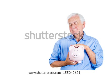 A close-up portrait of a retired old man with grey hair, holding a piggy bank, looking very serious, suspicious, possessive of his savings, isolated on a white background . Smart financial decisions.