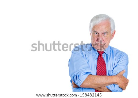 A close-up portrait of a senior executive, elderly man, grandfather with a very skeptical attitude, angry and mad, isolated on a white background with copy space. Human personalities, conflict  - stock photo