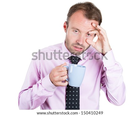 A close-up portrait of a very tired, almost falling asleep businessman holding a cup of coffee, struggling not to crash and stay awake, keeping his eyes opened, isolated on a white background  - stock photo