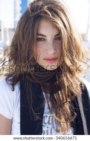 A close up portrait of a young beautiful girl with natural brunette hair and clean skin enjoying summer.