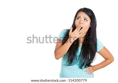 A close-up portrait of an attractive young female with yawn gesture, isolated on a white background with copy space - stock photo