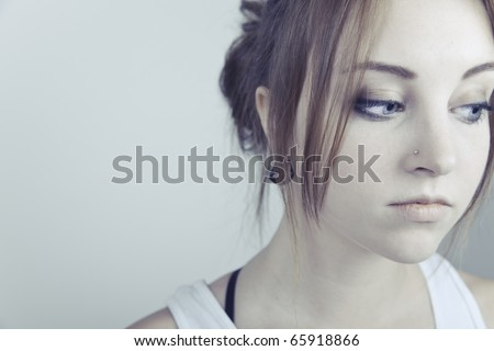 A close-up portrait of an attractive young woman with a sad look on her face. - stock photo