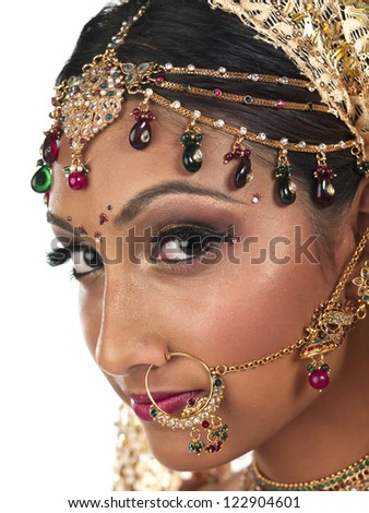 A close-up portrait of an Indian lady full of jewelry on a white background