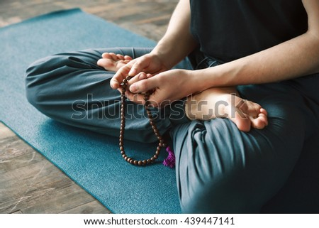 A close up portrait of man's hands holding string and sitting in lotus asana, yoga position, copy space.