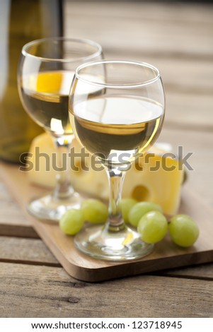 A close-up portrait of white wine with green grapes and slice of cheese over a wooden table