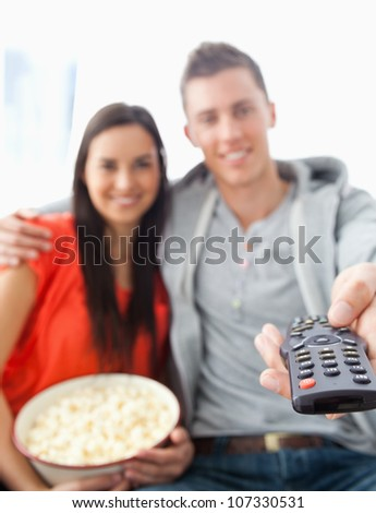A close up shot focused on the tv remote in the man's hand as he sits with his girlfriend on the couch - stock photo