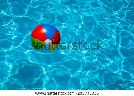 A close up shot of a beach ball floating in a cool blue summer pool.