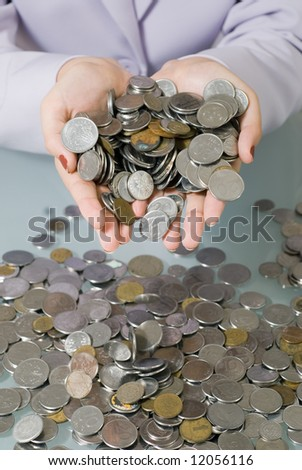 A close-up shot of a businesswoman holding coins above a pile of coins on glass desk. - stock photo