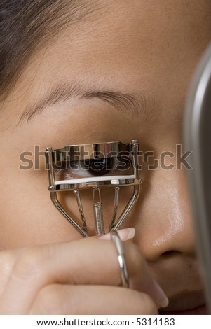 A close up shot of a girl curling her eyelashes
