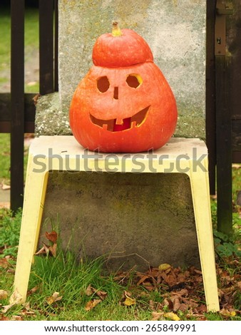 A close up shot of a happy jack-o-lantern sitting on a chair in front of house gate. - stock photo