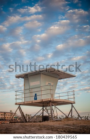 A close up shot of a life guard tower in Huntington Beach with a cloudy blue sky. - stock photo